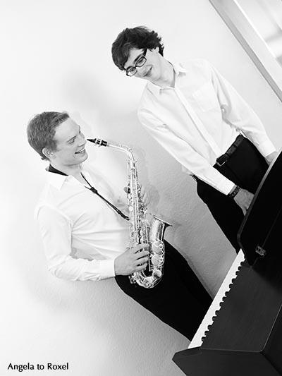 Fotografie: Zwei junge Musiker spielen Saxophon und Klavier, musizieren gemeinsam, machen zusammen Musik und haben Spaß, diagonal, schwarzweiß 2012