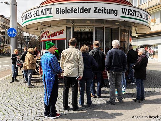 Clown steht in einer Warteschlange vor einem Kiosk am Jahnplatz, Spontanität an einem Samstag in der Bielefelder Innenstadt - Bielefeld, April 2016
