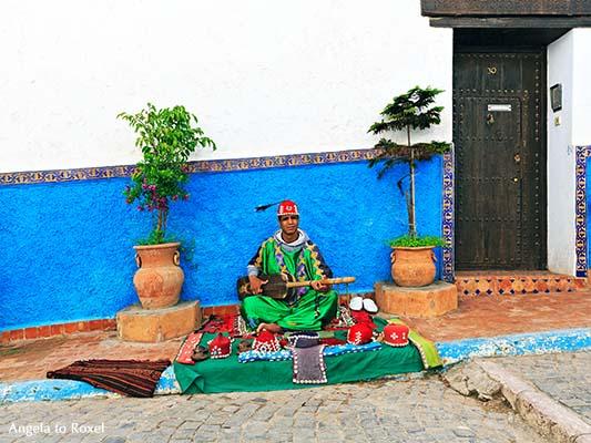 Gnawa-Musiker spielt auf der Sintir, vor einem blau und weiß gestrichenen Haus in der Kasbah des Oudaïas, Altstadt von Rabat - Marokko 2013