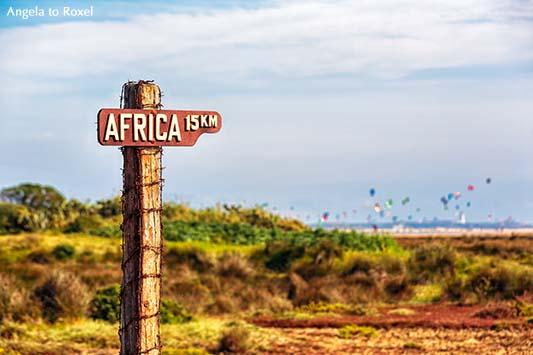 Wegweiser in Tarifa: 15 km bis Afrika - Schild am Campingplatz Rio Jara, im Hintergrund der Strand und die Kitesurfer von Tarifa, Cádiz, Spanien