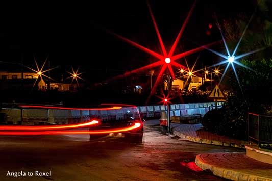 Auto rast in der Nacht durch eine Kurve auf eine rote Ampel zu, hohe Geschwindigkeit, Langzeitbelichtung mit Lichtspuren, Andalusien - Angela to Roxel