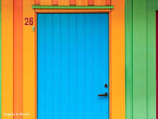Blaue Tür in der bunten Straße Øvre Holmegate im Zentrum von Starvanger, farbenfrohe Holzfassaden in Norwegen