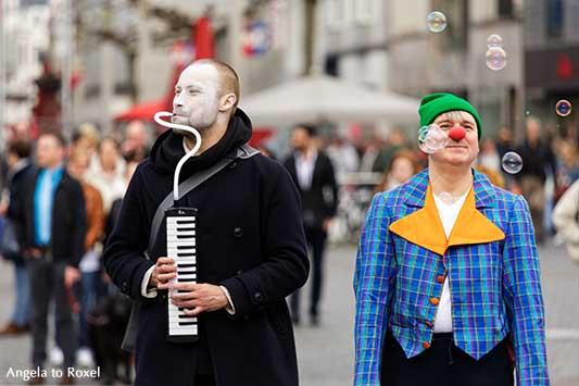 Zwei Clowns mit Musikinstrument und Seifenblasen, Walkact mit Clowns in der Innenstadt, Spontanität am Jahnplatz in Bielefeld | Angela to Roxel