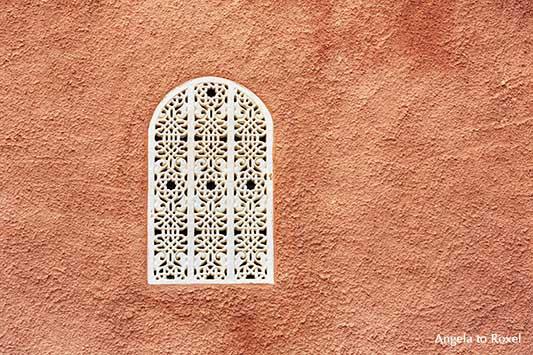 Fenster in Cortijo Cabrera, maurischer Baustil, weißes Fenstergitter mit arabeskem Muster in terrakottafarbener Wand, Turre, Andalusien - Angela to Roxel