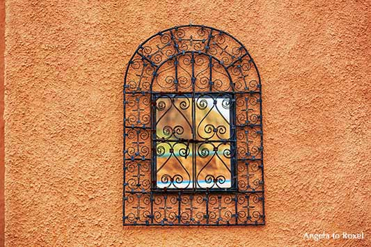 Arabeskes Gitter vor einem Spiegel in einem terrakottafarbenen Patio in Cortijo Cabrera, maurischer Baustil in Andalusien, Spanien - Angela to Roxel