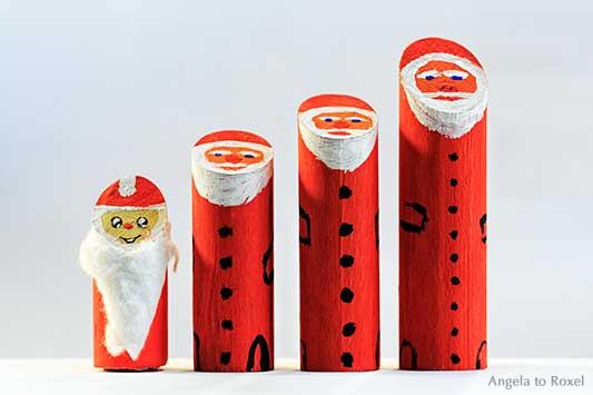 Vier Weihnachtsmänner aus Holz, rot bemalt, nebeneinander, der Größe nach sortiert, Weihnachtsdekoration | Fotografien kaufen - Angela to Roxel