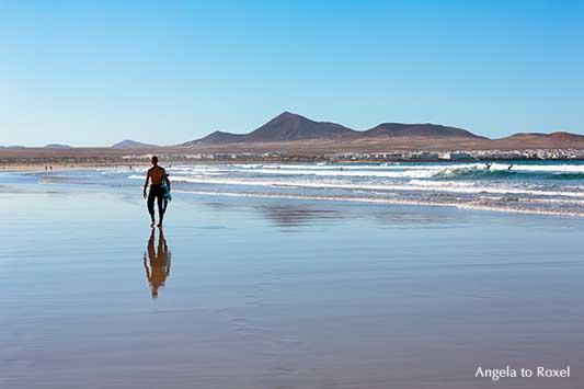 Famara Beach, langer weißer Sandstrand und Hotspot für Surfer auf Lanzarote, dahinter La Caleta de Famara und die Feuerberge | Angela to Roxel